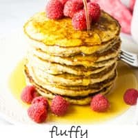 A stack of oat flour pancakes with maple syrup and raspberries on a white plate with syrup being poured over them