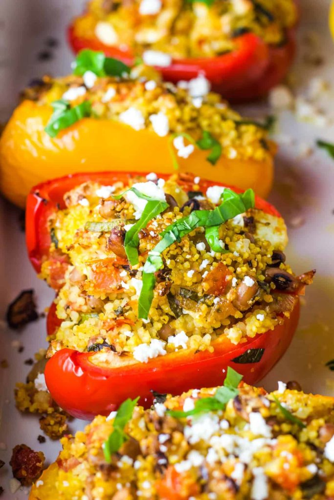Stuffed bell peppers sprinkled with basil in a baking dish