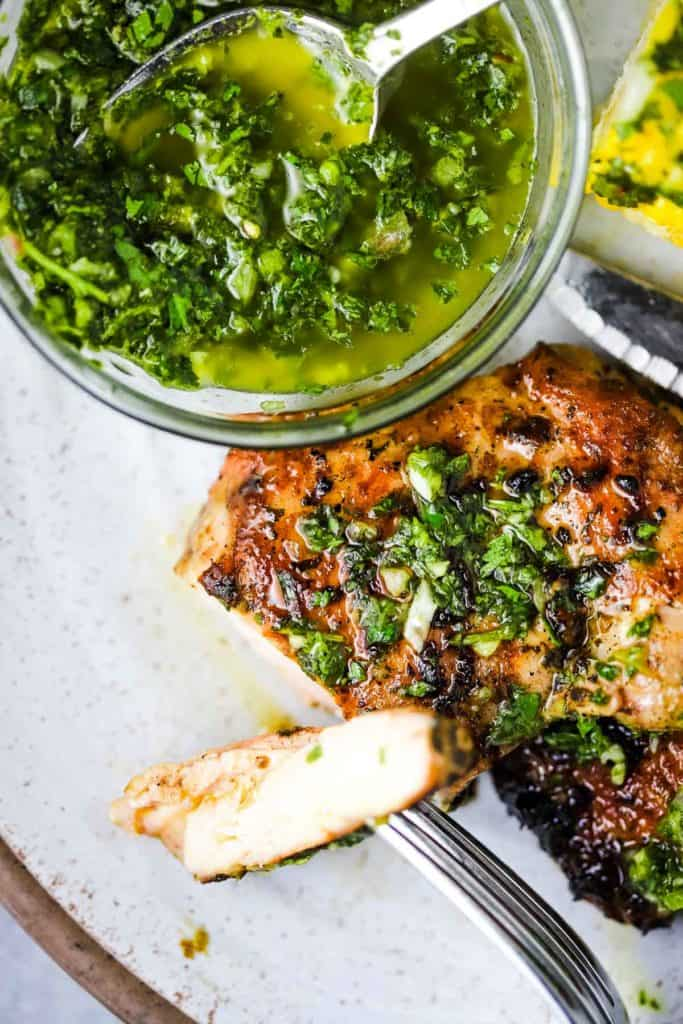 A chicken thigh with a slice on a fork, and a bowl of chimichurri