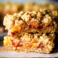 Two peach and raspberry oatmeal bars stacked on top of parchment paper
