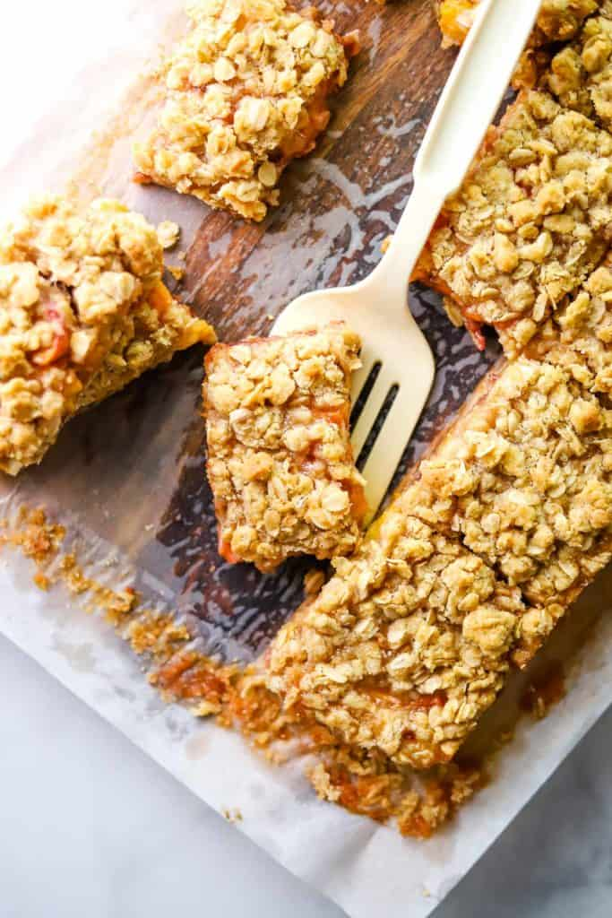Peach and raspberry oatmeal bars on parchment with a spatula picking one up