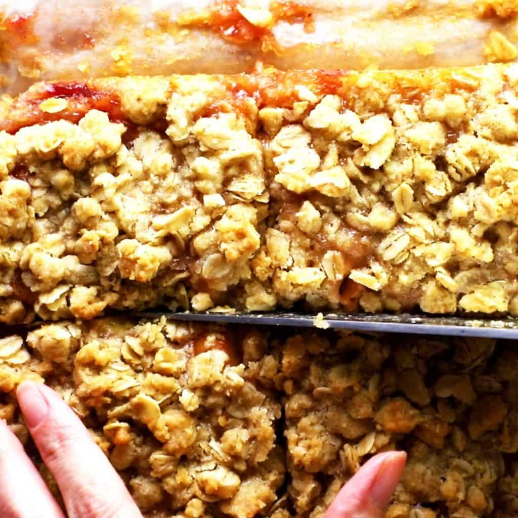 Raspberry and peach oatmeal bars being cut into squares with a knife