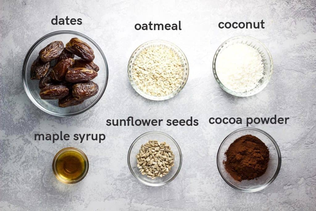 Ingredients needed to make date energy balls, laid out in glass bowls with labels