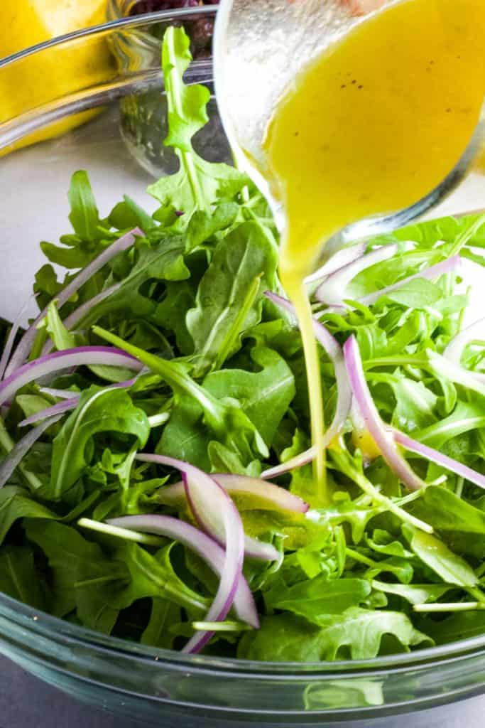 White wine vinaigrette being drizzled over arugula and thinly sliced onions