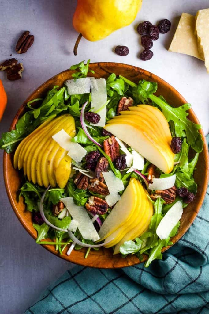 A salad composed of arugula, sliced pears, pecans, dried cranberries, and Parmesan shavings