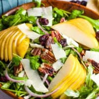 A rocket salad in a wooden bowl wit sliced pears, pecans and Parmesan shavings.