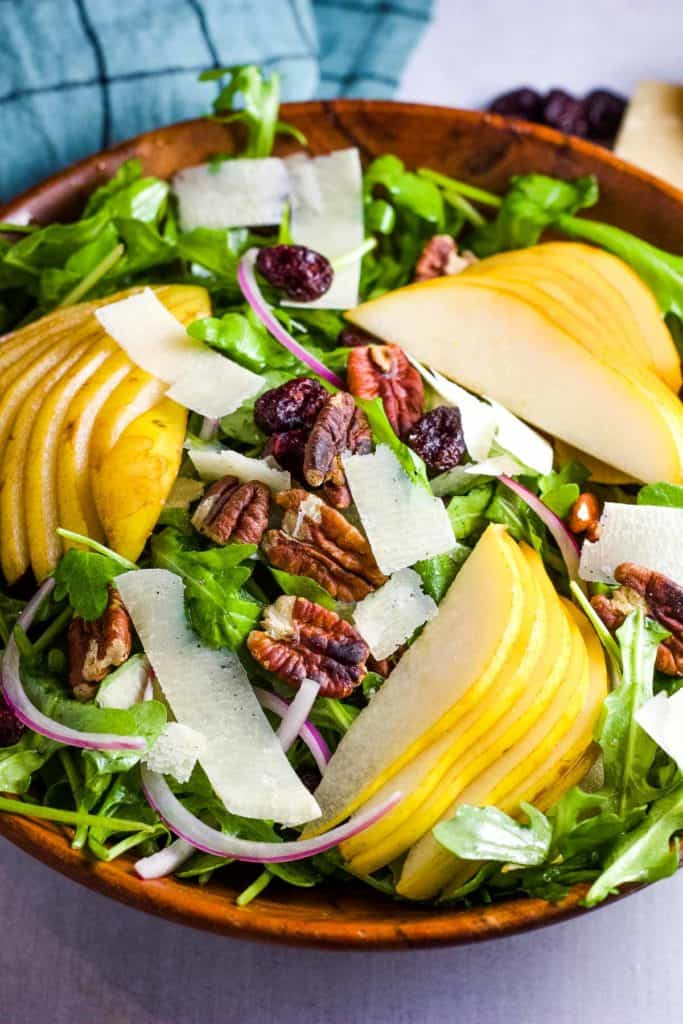 Slice pears arranged on a bed of arugula with pecans, shaved parmesan and sliced red onions.