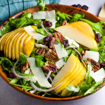 Sliced pears arranged on a bed of arugula with pecans, shaved parmesan and sliced red onions.