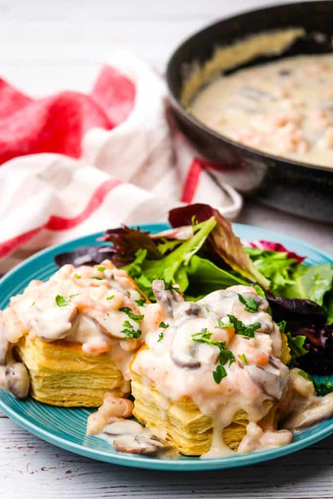 A plate of shrimp and mushroom vol-au-vents with sauce in pan in the background.