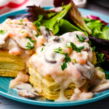Shrimp and mushroom vol-au-vents on a blue plate with salad