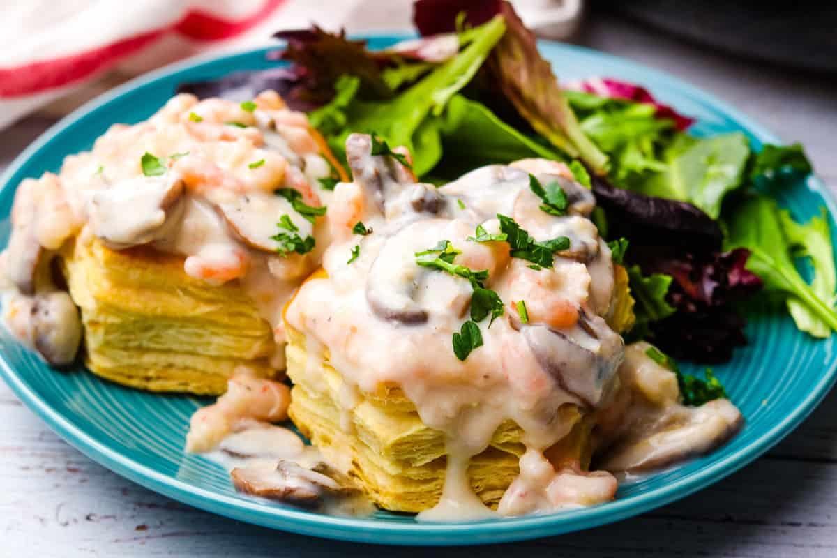 Shrimp and mushroom vol-au-vents on a blue plate with salad