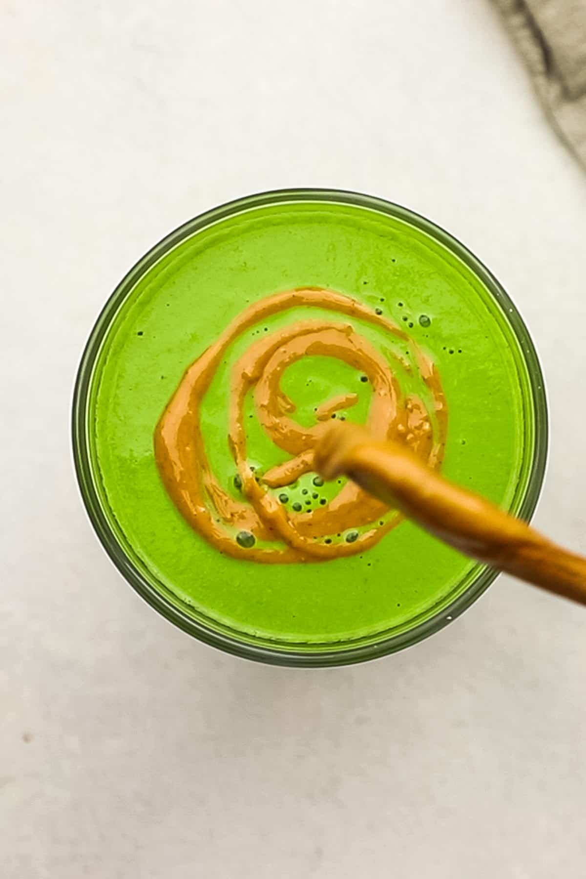 A peanut butter swirl being added to the top of a green smoothie