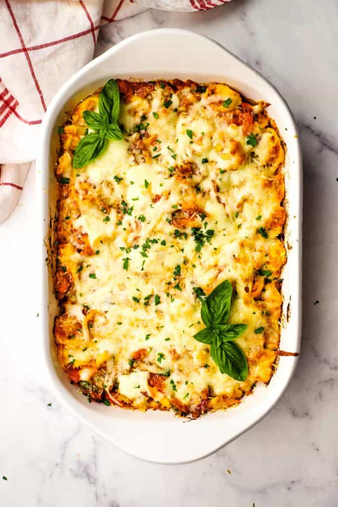 Baked tortellini in a white baking dish garnished with basil.